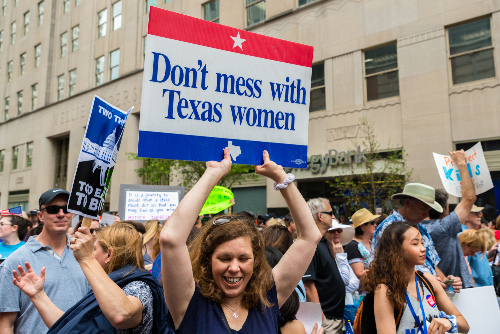 Marchers with one holding a sign that reads Don't Mess With Texas Women