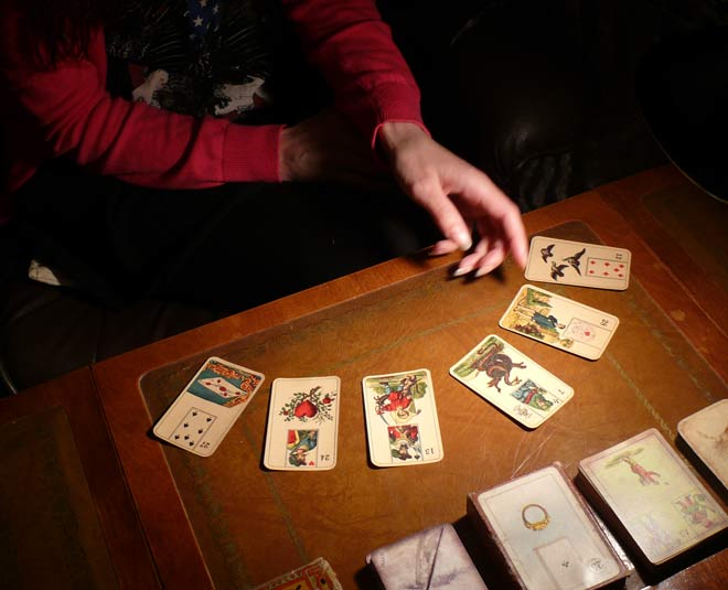 Person dealing tarot cards on a table